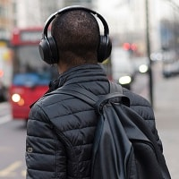 man wearing noise canceling headphones on road