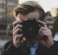 person holding a canon camera.