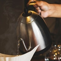 person pouring water from stainless steel kettle