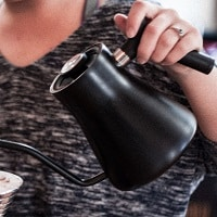 woman pouring from electric kettle