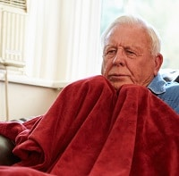Old man using a red blanket