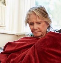 Old woman using a red blanket