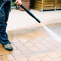 man washing the floor with a pressure washer