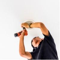 man installing ceiling speaker