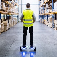 man riding a hoverboard in the warehouse