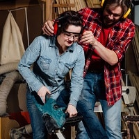 Carpenter woman and man with electric chainsaw in workshop
