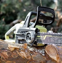 Electric chainsaw on the wooden log