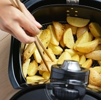Person picking potato chips out of an air fryer