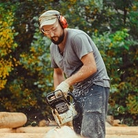 person using a chainsaw with headphones on