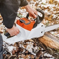 Man hands holding an electric chainsaw.