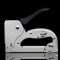 silver staple gun with black background