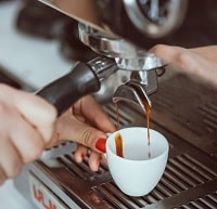 Professional espresso machine pouring fresh coffee into white ceramic cup