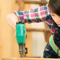 Asian woman using a nail gun