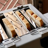 Slice of bread in the toaster for breakfast meal in the room