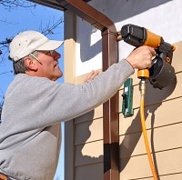 Man installing siding with nail gun