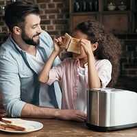 father and daughter with a bread machine