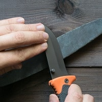 sharpening survival knife on a stone