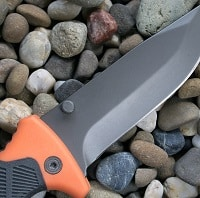 survival knife on a pebbles rocks stones