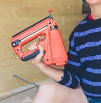 Young woman with nail gun